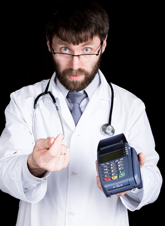 he is different: close-up portret of a Doctor holding pos-terminal, stethoscope around his neck. He rubs his thumb and forefinger, offering to pay. different emotions.
