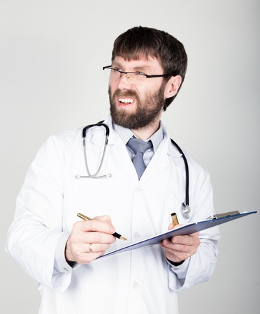 he is different: close-up portret of a Doctor holding a map-case for note, stethoscope around his neck. he discontentedly looking at the camera. different emotions.