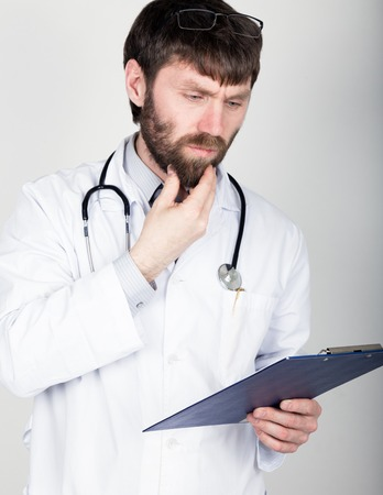 he is different: close-up portret of a Doctor holding a map-case for note, stethoscope around his neck. He rubs his chin. different emotions. Stock Photo