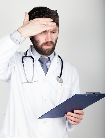 he is different: close-up portret of a Doctor holding a map-case for note, stethoscope around his neck. He wipes his forehead. different emotions.