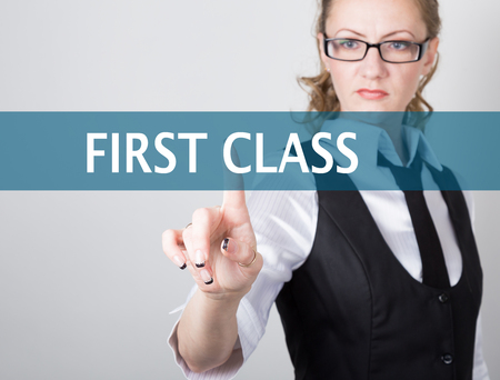internet class: first class written on a virtual screen. Internet technologies in business and tourism. woman in business suit and tie, presses a finger on a virtual screen.