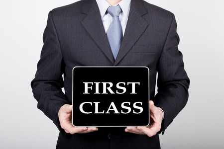 internet class: technology, internet and networking in business concept - businessman holding a tablet pc with first class sign. Internet technologies in business.
