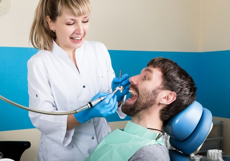 polymerization: The reception was at the female dentist. Doctor examines the oral cavity on tooth decay. Caries protection. Tooth decay treatment. Dentist working with dental polymerization lamp in oral cavity.
