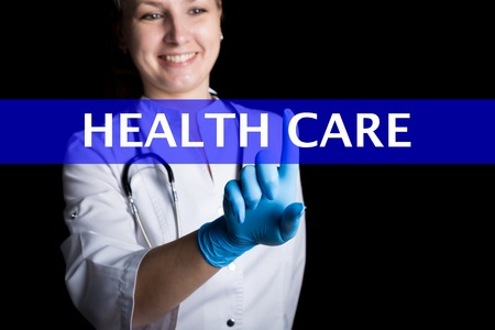 health care funding: Internet and technology concept. smiling female doctor presses a finger on a virtual screen. health care written on a virtual panel. Internet technologies in medicine.