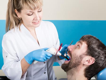 caries dental: La recepci�n estaba en el dentista femenina. El doctor examina la cavidad oral sobre la caries dental. Caries protecci�n. tratamiento de la caries dental. Dentista que trabaja con la l�mpara de polimerizaci�n dental en la cavidad oral.