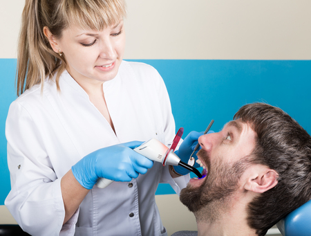 dental tools: The reception was at the female dentist. Doctor examines the oral cavity on tooth decay. Caries protection. Tooth decay treatment. Dentist working with dental polymerization lamp in oral cavity.