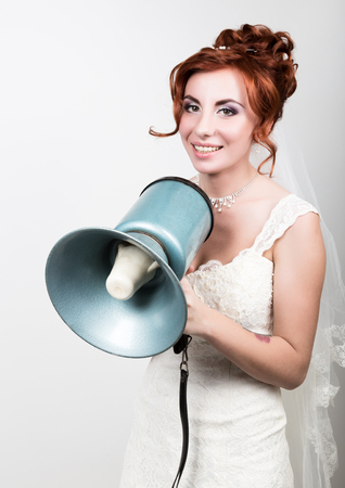 yells: beautiful bride in a wedding dress with a wedding makeup and hairstyle, she yells into a bullhorn. Public Relations. Stock Photo