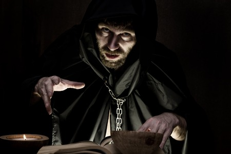 exorcist: necromancer casts spells from thick ancient book by candlelight on a dark background. Stock Photo