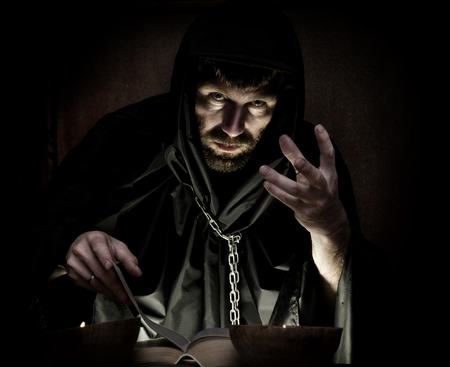 necromancer: necromancer casts spells from thick ancient book by candlelight on a dark background. Stock Photo