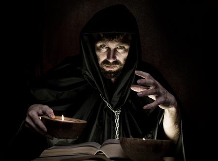 inquisition: necromancer casts spells from thick ancient book by candlelight on a dark background. Stock Photo
