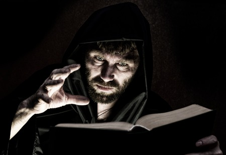 spells: necromancer casts spells from thick ancient book by candlelight on a dark background. Stock Photo