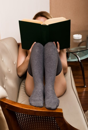 beautiful woman reading a thick book lying on the sofa.