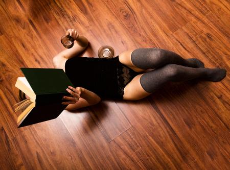 pantimedias: hermosa mujer leyendo un libro grueso tendido en el piso y beber café. Foto de archivo