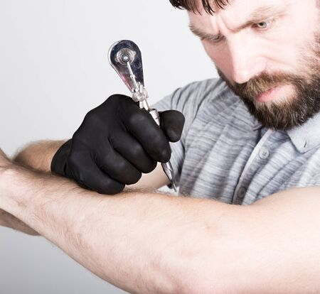 black gloves: close-up of Tattooist hands in black gloves with tattoo machine.