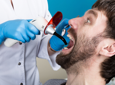 oral cavity: The reception was at the female dentist. Doctor examines the oral cavity on tooth decay. Caries protection. Tooth decay treatment. Dentist working with dental polymerization lamp in oral cavity.
