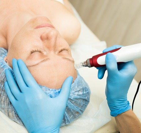 fractional: Beautician makes fractional mesotherapy to young woman. The cosmetic procedures for the face. Beauty treatments in the spa salon. Facial Skin Care.