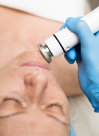 fractional: Beautician makes RF-lifting to young woman. The cosmetic procedures for the face. Beauty treatments in the spa salon. Facial Skin Care.
