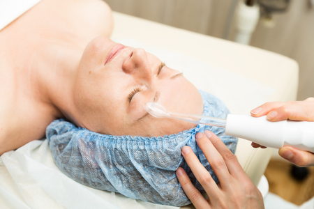 fractional: Beautician makes darsonvalization to young woman. The cosmetic procedures for the face. Beauty treatments in the spa salon. Facial Skin Care.