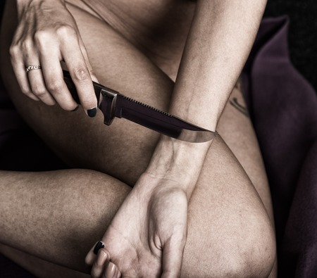 lacerate: Suicide attempt of a hand cutting a wrist with a knife. Focus on hand. Stock Photo