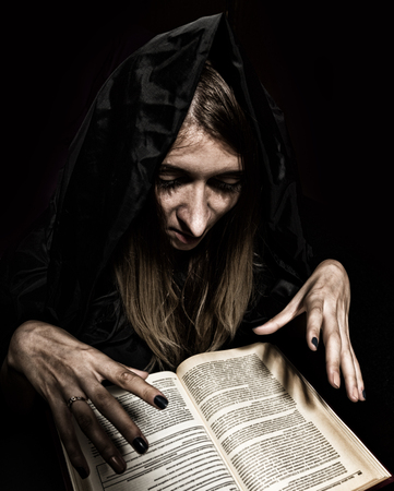 black magic: pretty witch casts spells from thick ancient book by candlelight on a dark background. Stock Photo