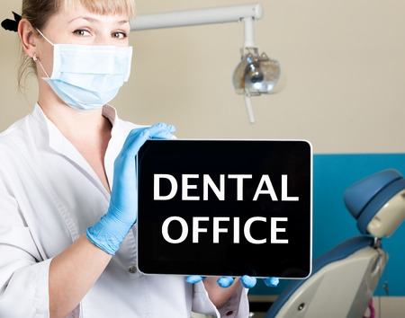 dental calculus: technology, internet and networking in medicine concept - femail dentist holding a tablet pc with dental office sign. at the dental equipment background.