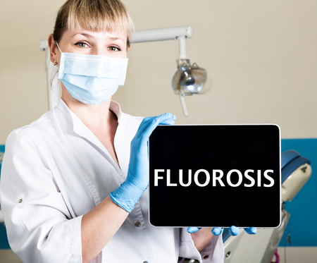 technology, internet and networking in medicine concept - femail dentist holding a tablet pc with fluorosis sign. at the dental equipment background.