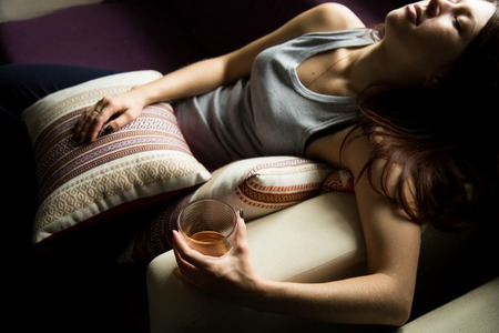 addictive drinking: sad lonely woman drinks alcohol in the dark. Glass in sharp focus. female alcoholism. Stock Photo