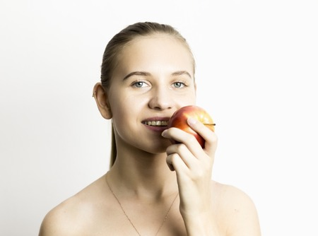 nude little girls: beautiful naked young woman eating an apple. healthy food - strong teeth concept.