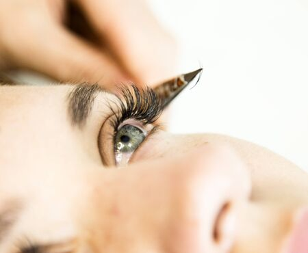 Beautiful young woman with eyelash extension. Woman eye with long eyelashes. Beautician eyelash extension for young woman in a beauty salon. Stock Photo
