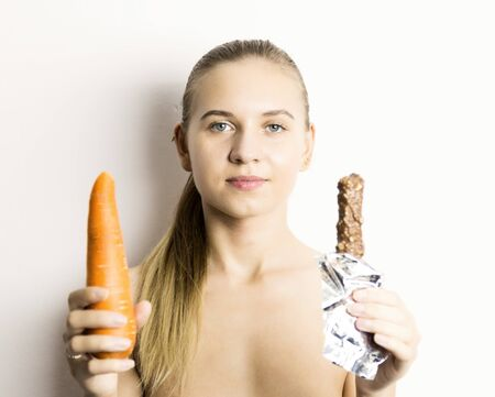 nude little girls: beautiful naked young woman eating an carrot. carrot vs chocolate. healthy food - strong teeth concept.
