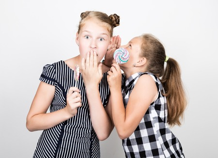pamper: Two cute little girlfriend eating bright lollipops. Funny kids. Best friends pamper and posing. one of them whispers secret in the ear. Stock Photo