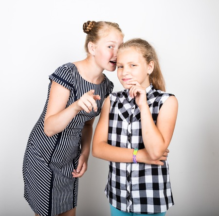 pamper: Two cute little girlfriend expressing different emotions. Funny kids. Best friends pamper and posing.