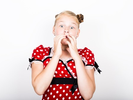 pamper: beautiful young girl dressed in a red dress with white polka dots. Funny kids pamper and posing.