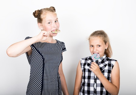 pamper: Two cute little girlfriend eating bright lollipops. Funny kids. Best friends pamper and posing. Stock Photo