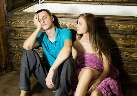 Plumber having flirt with young girl at home. men siting on a floor bathtub, tired and sleepy after flirt with young female customer.