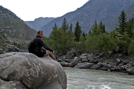 beach hunk: man sitting on a large rock over mountain river. Stock Photo