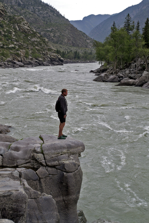 beach hunk: man standing on a large rock spread his arms over mountain river.