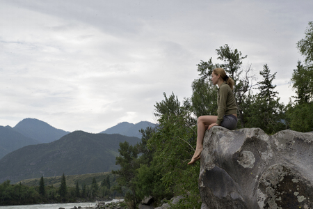beach hunk: young woman sitting on the edge of the cliff above the mountain river. Stock Photo