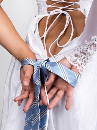 linked hands: Bride putting on her white wedding dress, closeup brides hands are linked male tie.