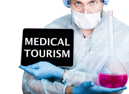 health care decisions: internet technology and networking in medicine concept. Doctor in surgical uniform, holding pink flask and digital tablet pc with medical tourism sign. Isolated on white.
