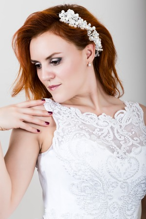 elegance fashion girls look sensuality young: red-haired bride in a wedding dress holding wedding bouquet, bright unusual appearance. Beautiful wedding hairstyle and bright make-up.