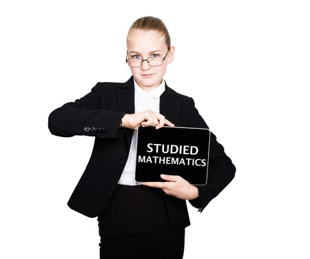 studied: Beautiful school girl in a business suit holds a pc tablet in his hands and looking into the camera, on a pc tablet inscription studied mathematics.