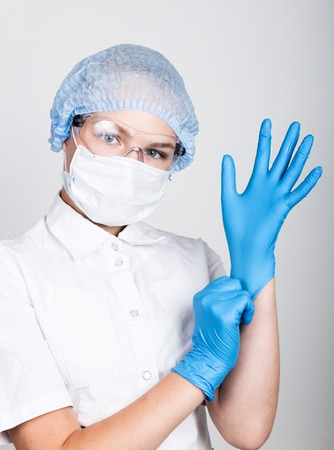 little girl dressed in medical clothes pulls into the hands medical gloves.