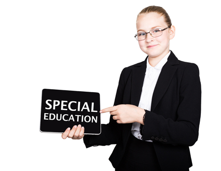 special education: school girl in a business suit holds a pc tablet in his hands and looking into the camera, on a pc tablet inscription special education.