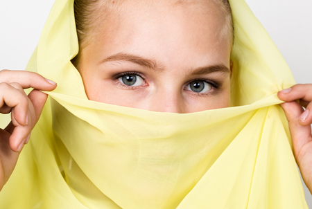 close-up beautiful mysterious eyes eastern woman wearing a yellow hijab. Stock Photo