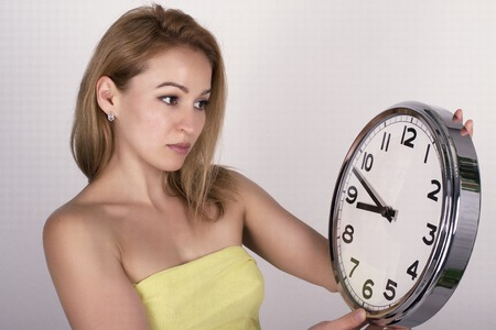 hasten: Beautiful young woman looking at a large silver retro clock that she is holding, she wonders how much time passed