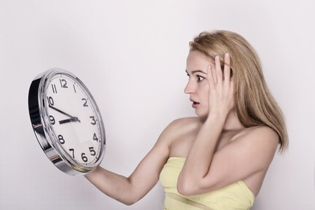 seconds: Beautiful young woman looking at a large silver retro clock that she is holding, she wonders how much time passed