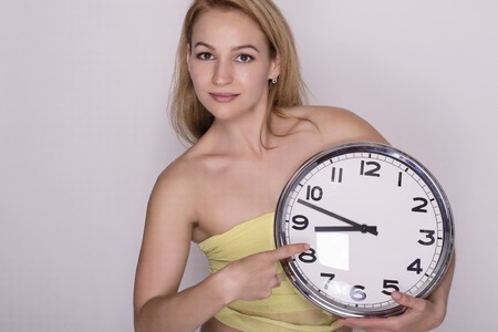 young beautiful woman holding big clock. time concept