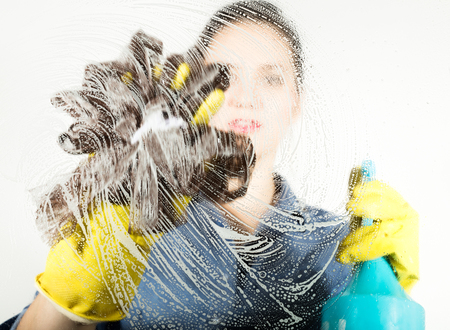 young housewife washed window with a spray, cloth and detergent. Large glass in foam. Housework concept