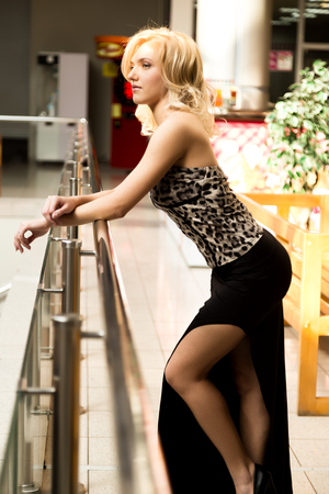 Beautiful girl standing near banister and looks around.